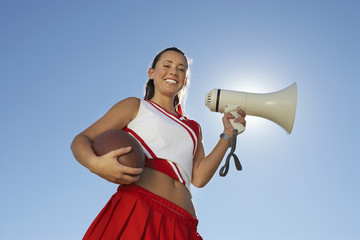 cheerleader holding football and megaphone low angle view portrait (portrait) (low angle view)