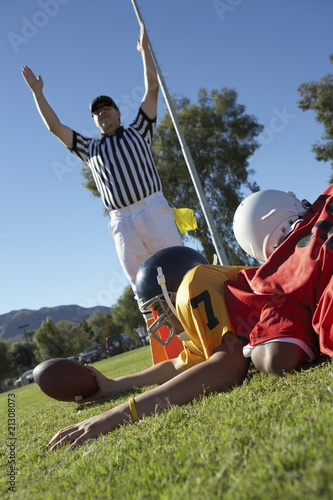 referee signalling touchdown over football player tackled in end zone