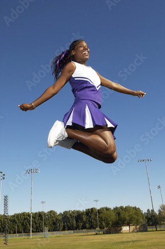 cheerleader jumping on field mid air low angle view (low angle view)