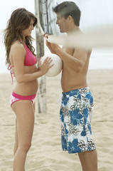 Couple Flirting on Beach under Volleyball Net