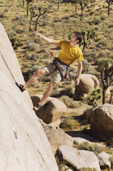 Climber Tugging on Rope on Cliff