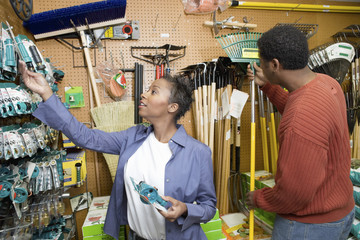 couple selecting garden tools in shop