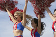 cheerleaders running holding pom poms in air