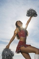 cheerleader doing routine with pom poms