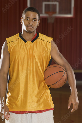 basketball player with ball on indoor court (portrait)