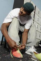 young man tying bowling shoes portrait