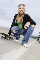 young female skateboarder crouching on pavement low angle view