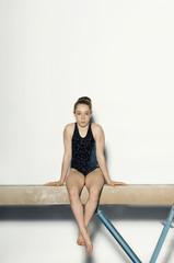 gymnast (13-15) sitting on balance beam portrait