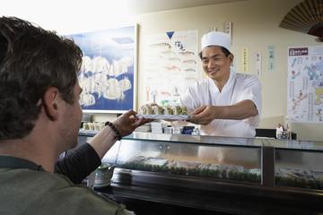 sushi chef handing sushi to customer in restaurant