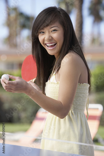 woman in summer dress playing ping pong