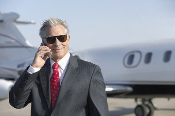 businessman standing on landing strip near private jet talking on mobile