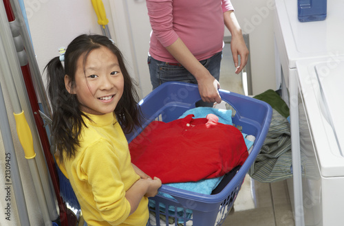 mother and daughter (7-9) doing laundry