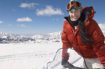 woman standing on snowmobile in snow half length