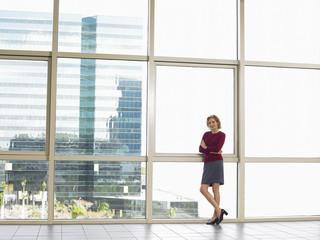 businesswoman by window in office building portrait