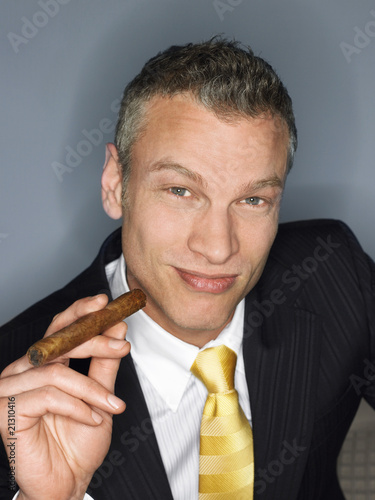 businessman holding cigar in studio