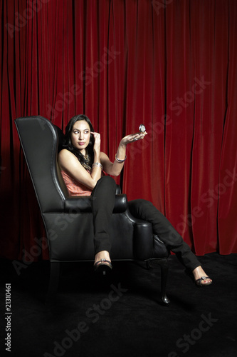 stylish woman sitting leg over arm in wingback chair checking make-up in compact mirror side view