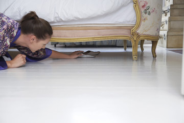 woman reaching for slippers under bed