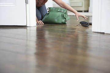 woman reaching for spilled purse on floor