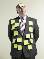 businessman with sticky notes stuck to suit