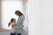 mother and daughter embracing standing in front of window