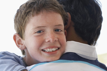father son hugging portrait of son head and shoulders