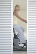 mature woman on exercise bike behind blinds pedalling side view
