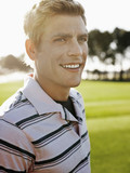 young male golfer on court smiling