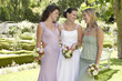 bride with two women in garden holding bouquets smiling portrait