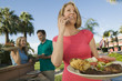 woman using mobile phone holding plate of food at family outdoor barbecue.