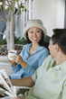 couple drinking coffee and reading newspaper outdoors