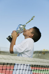 young tennis player by net on court kissing trophy side view