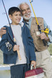 grandfather and grandson holding fishing rods outdoors smiling