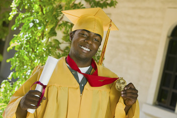 graduate holding diploma and medal outside portrait