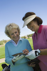 two women writing in score card on golf course