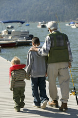 grandfather and two grandsons holding fishing rods walking on pier back view
