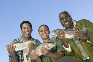 male members of three generation family showing fishes smiling (portrait)