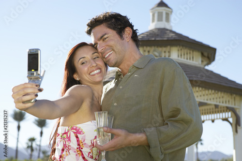 couple taking photograph of themselves with cell phone near pavilion