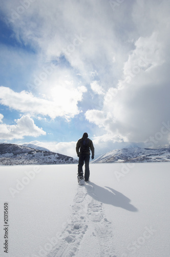 man walking in snowshoes through snow back view