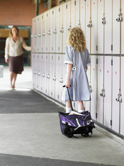 elementary schoolgirl walking towards mother along school lockers back view