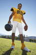 football player holding helmet and ball standing on field low angle portrait (portrait)