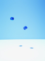 Blue dice in mid-air