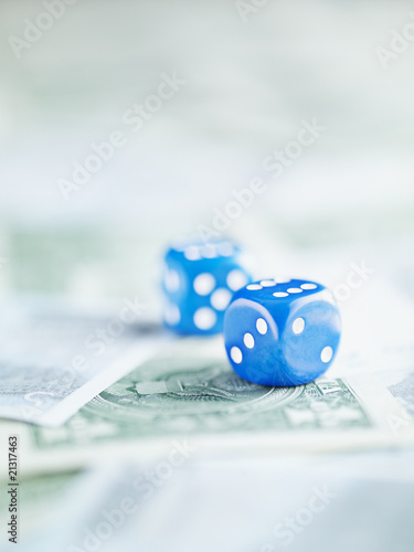 Blue dice on pile of dollar bills