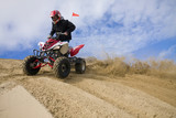 ATV rider spray sand in dunes