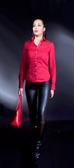 Beautiful brunette with red shirt and red bag  walking