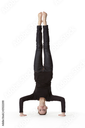 Teenage girl in headstand on white background