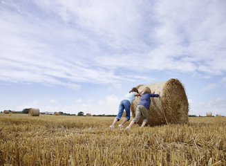 Two girls pushing bale of hay