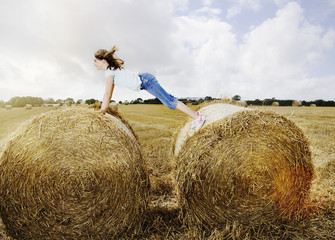Girl balancing between two bales of hay