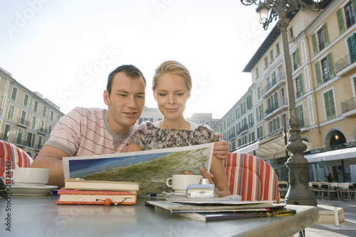 Man and woman at outdoor cafe reading map