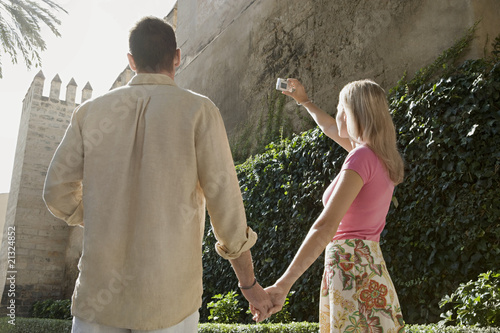 Man and woman holding hands using digital camera