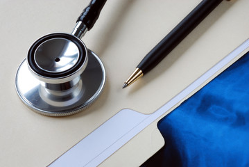 A stethoscope on the top of a medical folder